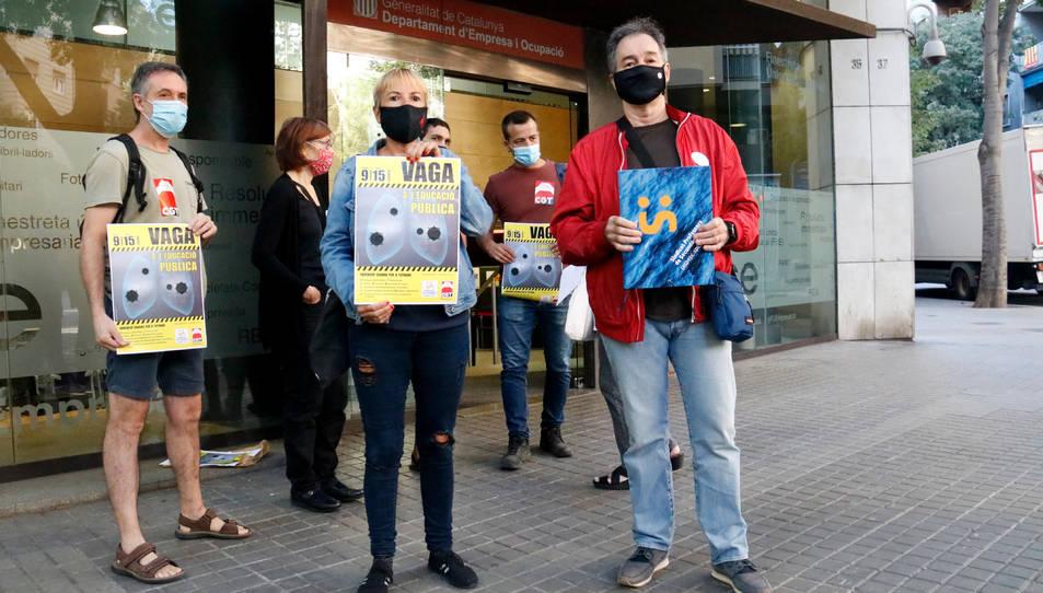 Marta Minguella, delegada de CGT Ensenyament, i Xavier Massó, secretari general de Professors de Secundària, mostren un cartell amb la convocatòria de vaga.