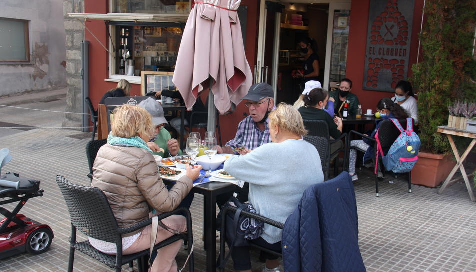 Pla obert on es veuen diverses persones a les taules d'una terrassa de bar