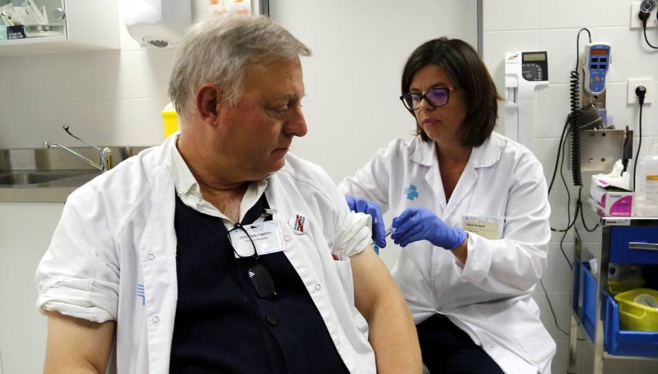 Un auxiliar d'infermeria vacunant-se per la grip.