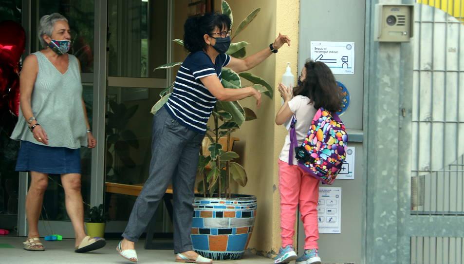 Una nena desinfectant-se les mans amb gel hidroalcohòlic a la porta de l'escola.