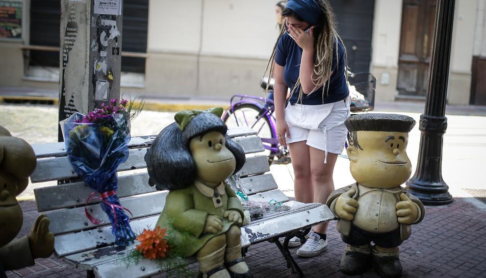 Una dona davant l'estàtua de Mafalda a Buenos Aires, Argentina.