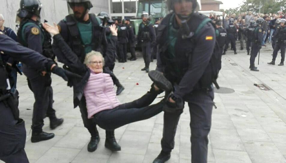 Una àvia es portada a braços per agents de la Guàrdia Civil en el desallotjament del col·legi electoral de la Ràpita.
