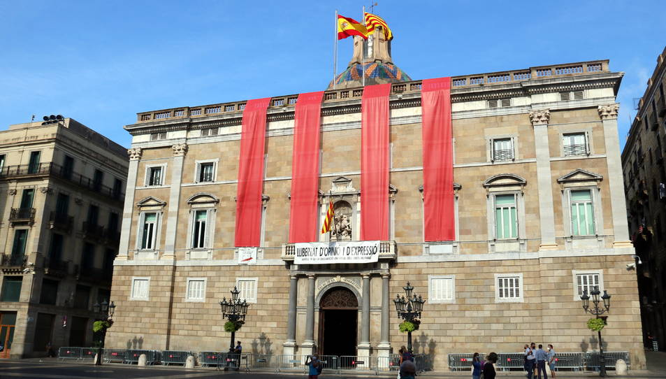 Façana principal del Palau de la Generalitat amb quatre grans lones verticals vermelles com les quatre barres per commemorar l'1-O.