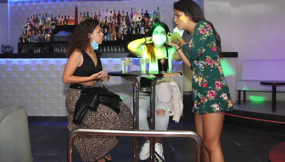 Pla sencer de tres clientes de la discoteca Totem, fent una copa en una de les taules que s'han col·locat.