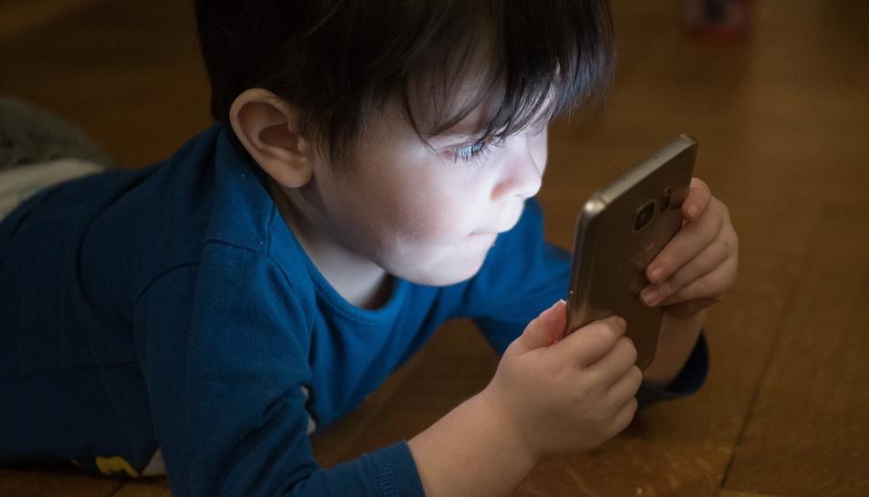 Un nen petit fixat amb una pantalla de mòbil.