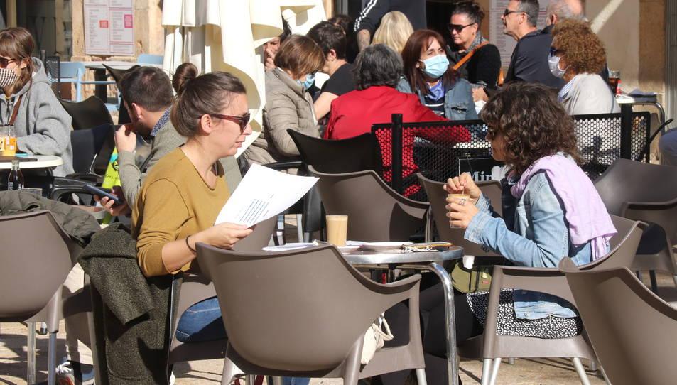 Dues persones en una terrassa d'un bar de la plaça de la Font de Tarragona.