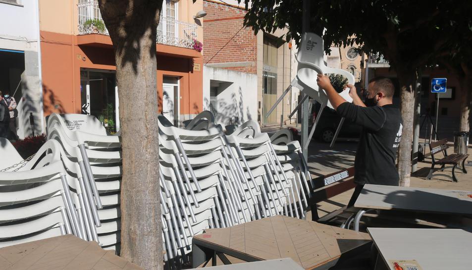El propietari d'un bar recollint cadires aquest 16 d'octubre del 2020.