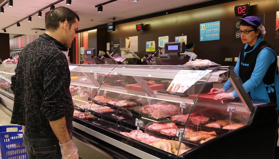 Un client amb guants comprant carn en un supermercat de l'Espai Gironès.
