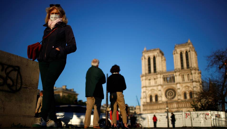 La gent amb mascaretes davant la catedral de Notre-Dame de Paris durant la pandèmia del coronavirus.