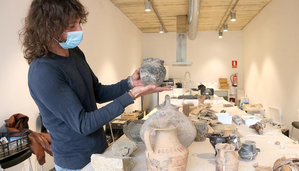 L'arqueòleg Dani López mostrant una peca de ceràmica sencera trobada al jaciment Font de la Canya.