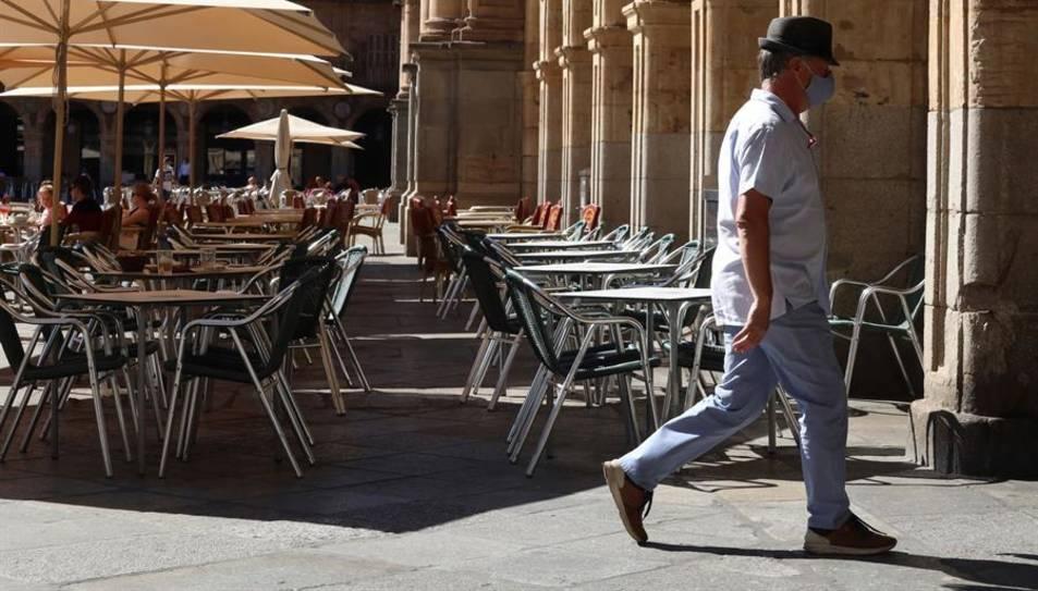 Un home amb mascareta passa davant d'una terrassa d'un restaurant de la plaça Major de Salamanca.