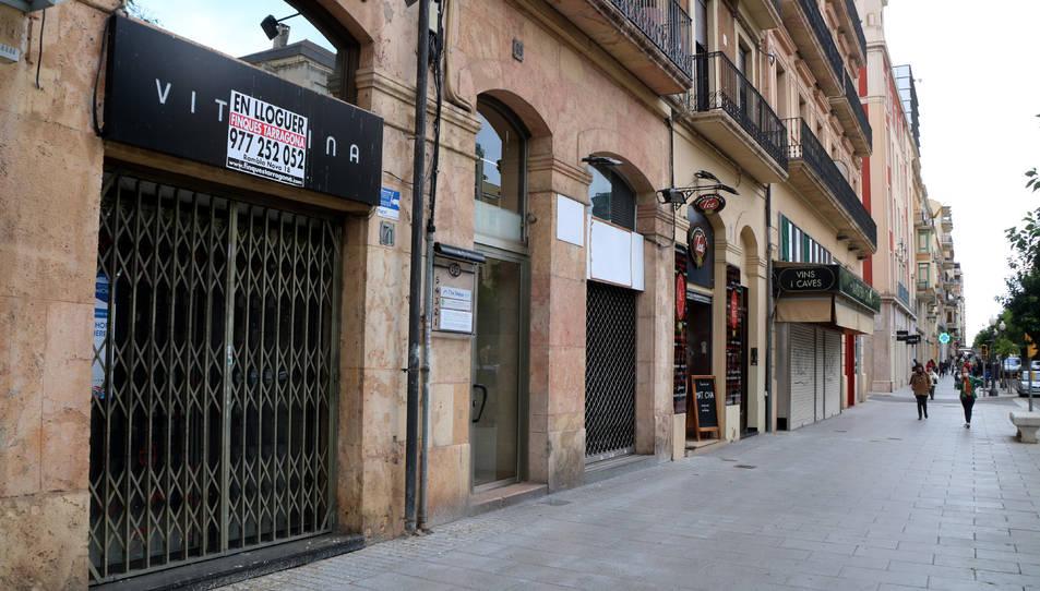 Una zona de la Rambla Nova de Tarragona on s'hi aprecien tres locals comercials buits, amb poc moviment de vianants.
