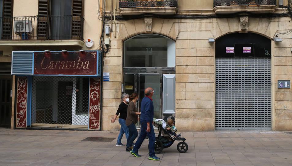 Dos locals tancats al carrer Sant Agustí de Tarragona amb un grup de persones caminant per davant