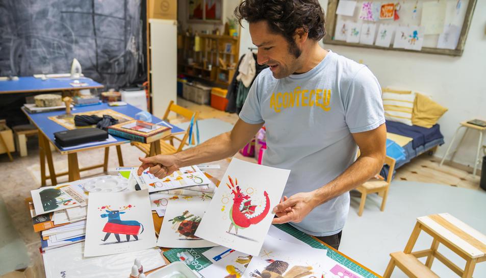 L'Armand al seu taller de Tarragona amb algunes làmines del llibre.