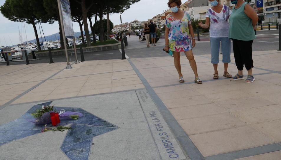 Tres dones observant unes flors i unes veles sobre el memorial commemoratiu dels atemptats terroristes, davant del Club Nàutic de Cambrils.