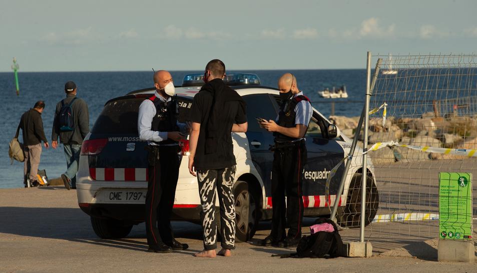 Els Mossos multant una persona a BArcelona per fer esport a una zona prohibida.