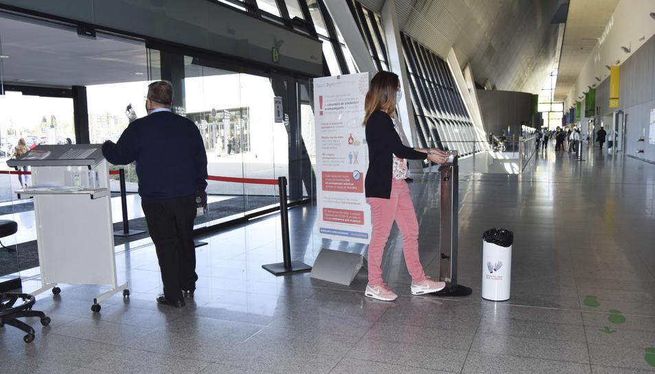Visitants accedint a l'Hospital de Reus, posant-se gel hidroalcohòlic a les mans, a la porta d'entrada.