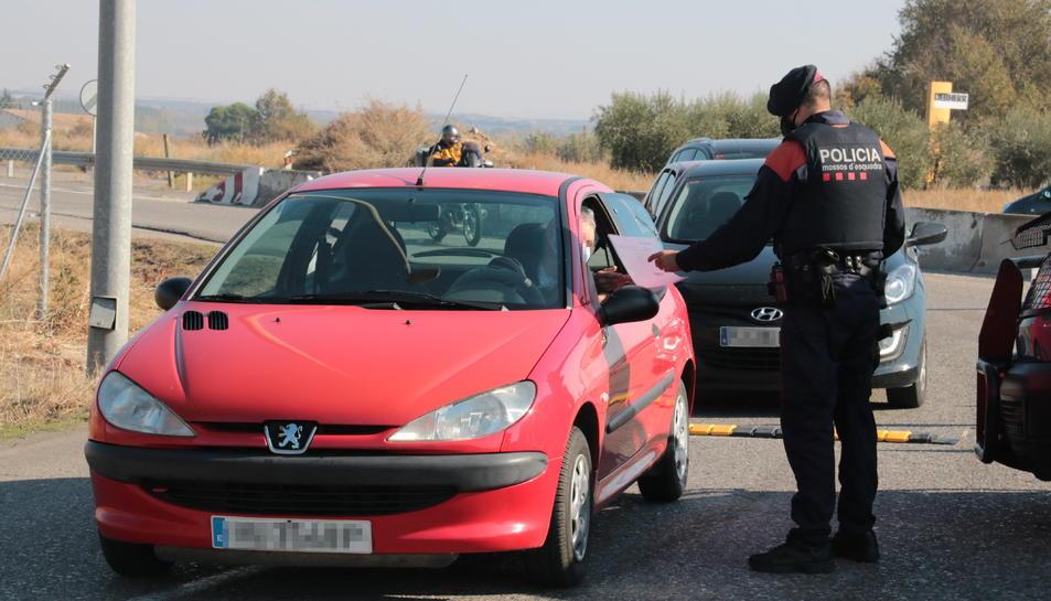 Una gent de l'ARRO dels Mossos d'Esquadra demanant tornant a un conductor un certificat d'autoresponsabilitat, durant un control a l'antiga N-II, al terme municipal d'Alcarràs