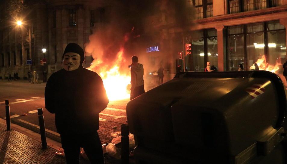 Nois gravant com un contenidor crema a la Via Laietana i un altre amb la mascareta d'Anonymous s'hi apropa, en els aldarulls després d'una concentració contra les restriccions per la segona onada de la covid-19