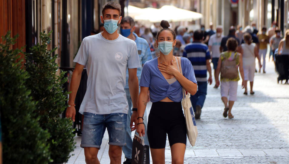 Pla americà d'un noi i una noia caminant amb mascareta pel carrer Monterols de Reus
