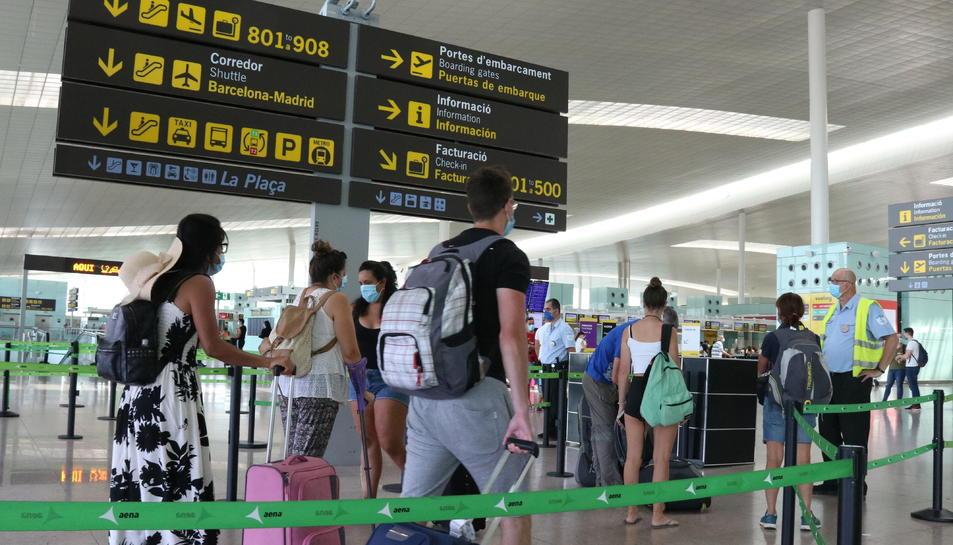 Pla general de passatgers fent cua per accedir a la T1 de l'Aeroport del Prat.