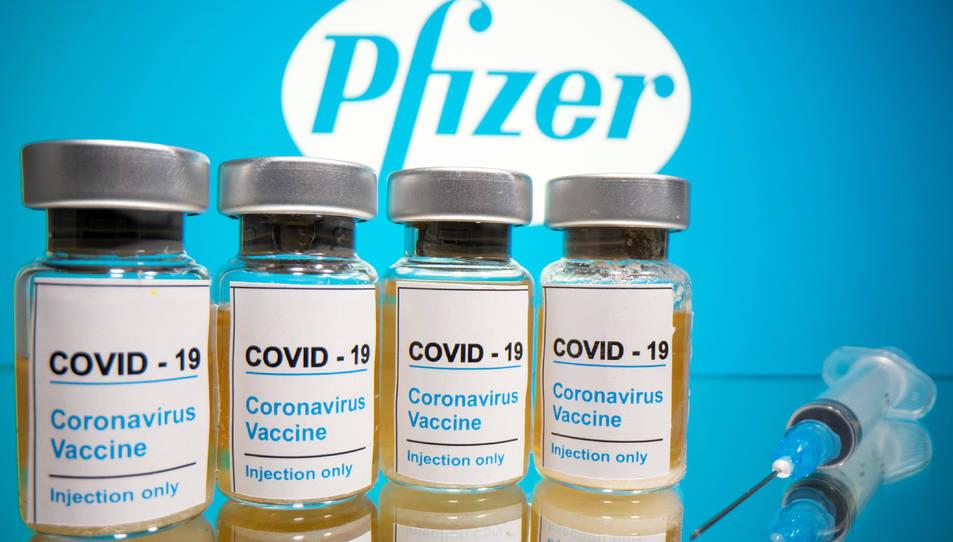Vials amb l'etiqueta «COVID-19 / vacuna contra el coronavirus / només per injecció» i una xeringa mèdica davant del logotip de Pfizer.