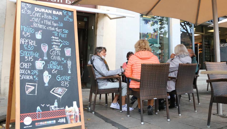 Un grup de persones consumint en una terrassa a Girona.