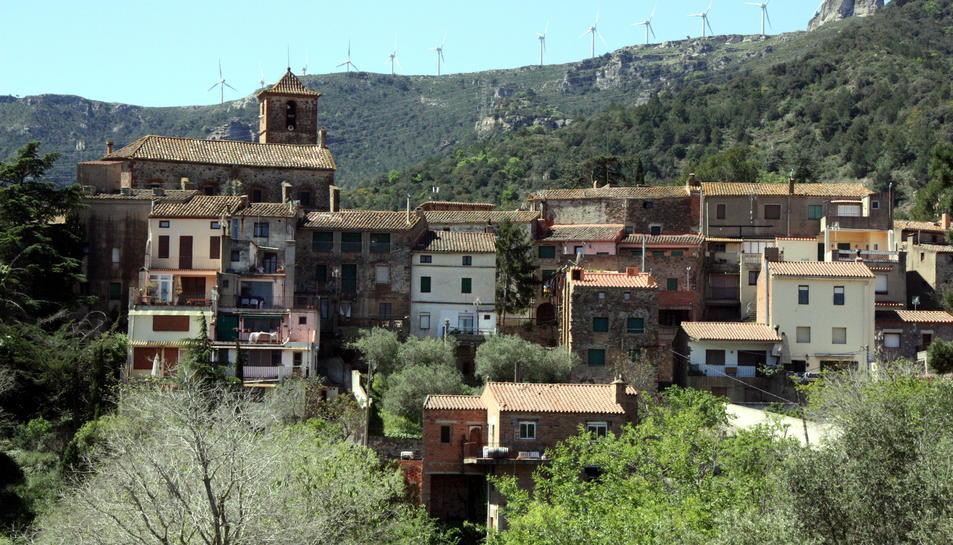 Pla general d'una panoràmica del poble de l'Argentera, al Baix Camp, amb l'església sobresortint d'entre els edificis i, al fons al darrere, molins d'energia eòlica damunt la muntanya
