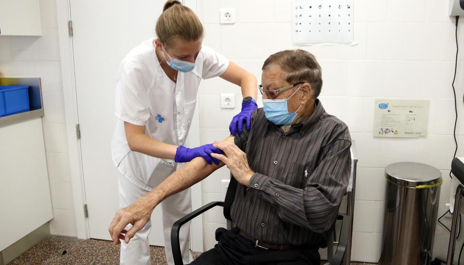 Un home posant-se la vacuna contra la grip a Figueres