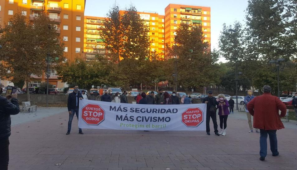 Alguns dels participants a la convocàtoria sostenen una pancarta on s'exigeix una major seguretat al barri