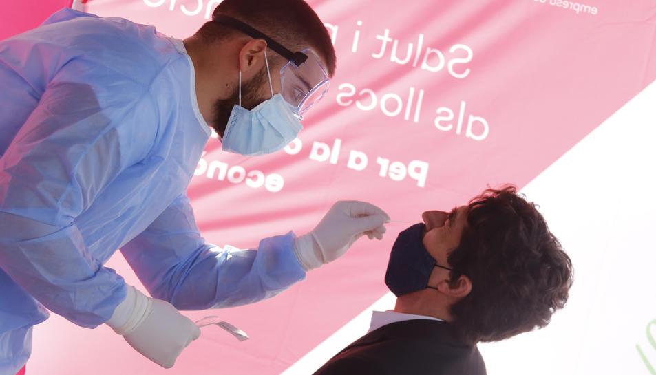 Personal sanitari pren mostres a un treballador del polígon de Sant Quirze del Vallès per fer un test d'antígen