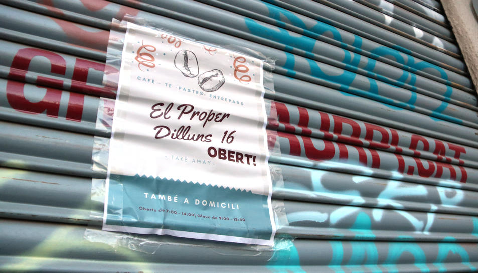 Un cartell en la persiana d'un local al centre de Sabadell anunciant la reobertura, el 22 de novembre de 2020