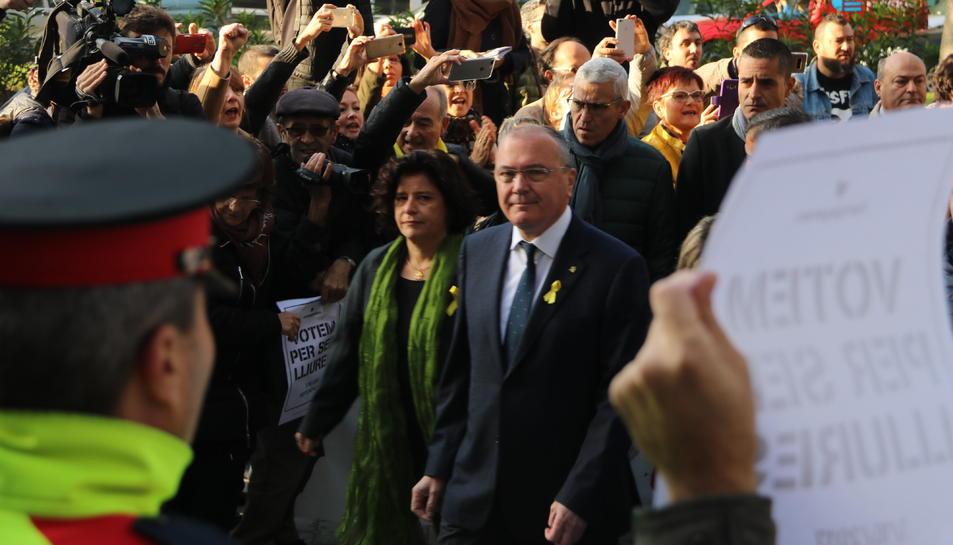 Pla mig de l'alcalde de Reus, Carles Pellicer, amb la regidora Montserrat Vilella, entrant al jutjat de Reus enmig de diversos manifestants.
