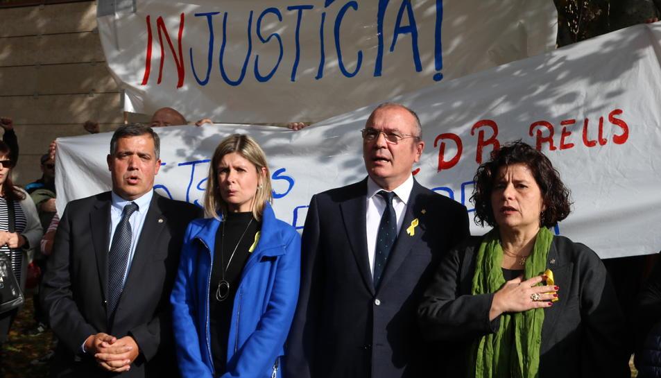 Pla mig de tres dels portaveus investigats i l'alcalde, cantant 'Els Segadors' a la sortida del jutjat de Reus.