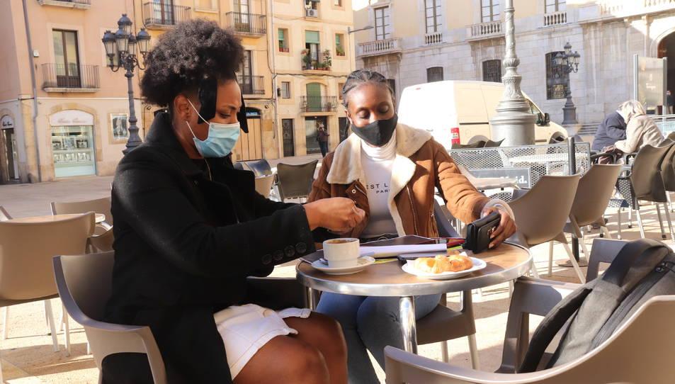 Dues noies fent un cafè en una terrassa de la plaça de la Font de Tarragona.