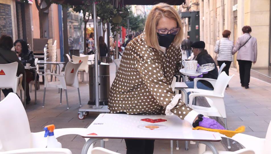 Primer pla d'una restauradora netejant una taula al carrer August de Tarragona.