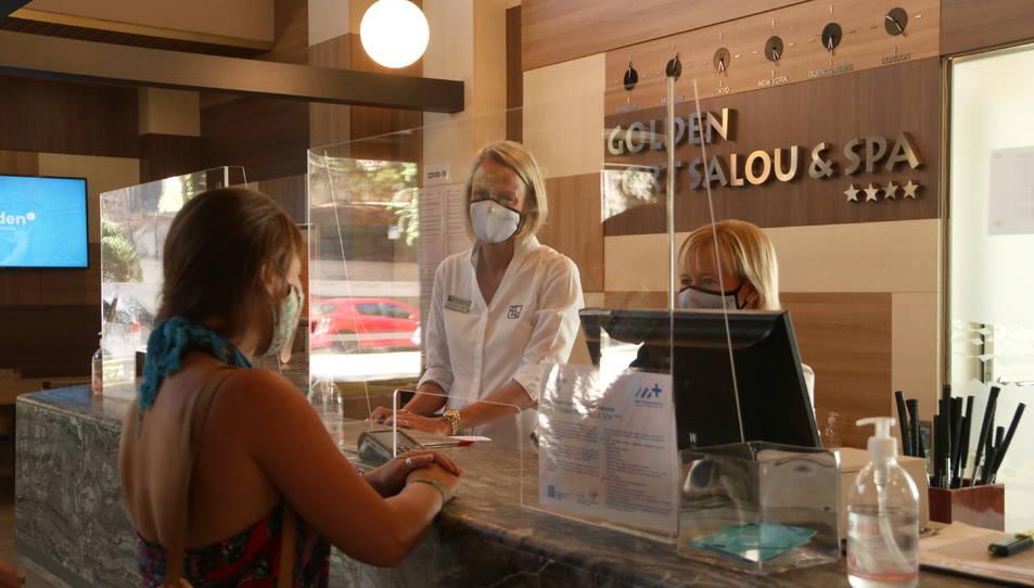 Una turista i dues treballadores a la recepció d'un hotel de Salou.