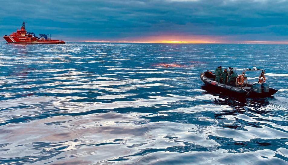Agents de la Guàrdia Civil en primer terme amb el vaixell de Salvament Marítim Clara Campoamor al fons.