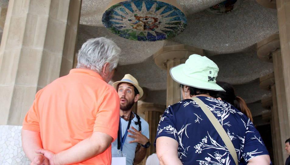 Un guia turístic donant explicacions a un grup de persones a la sala Hipòstila del Parc Güell.