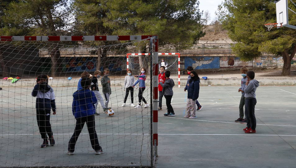 Nens jugant a futbol durant l'hora d'esbarjo al pati de l'escola.