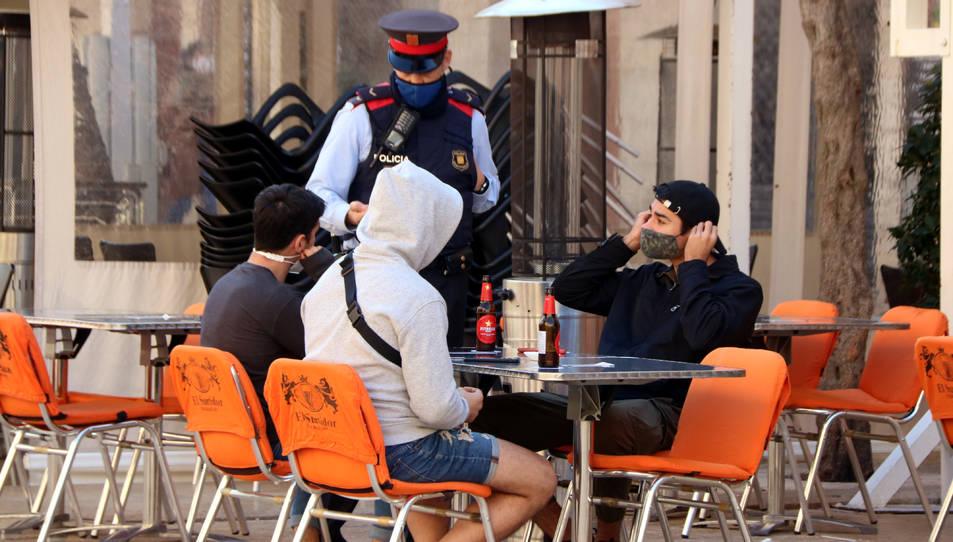 Un agent demanant a diversos clients d'un restaurant de la plaça de la Font que es posin la mascareta mentre no consumeixin