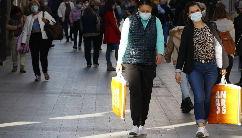 Unes noies amb bosses, comprant al carrer de Llovera de Reus, en primer terme, i al fons, gent passejant-hi.
