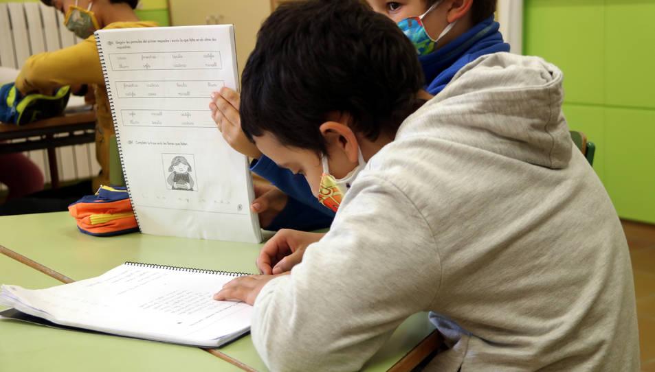 Pla mitjà d'uns alumnes fent classe a l'escola.