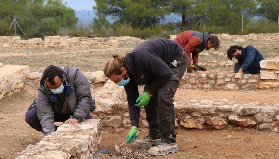 Arqueòlegs treballant en la consolidació de les restes de cases excavades al Castellet de Banyoles.