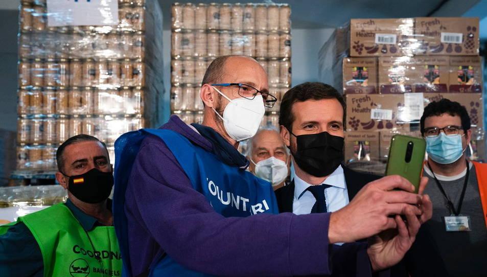 El president del PP, Pablo Casado, consultant el telèfon mòbil d'un voluntari del Banc d'Aliments de Reus.