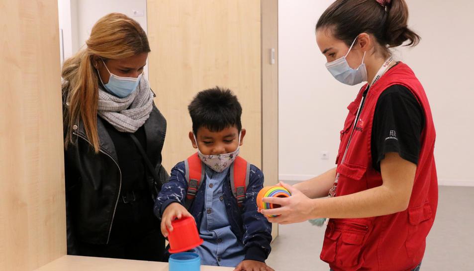 En Fèlix, el nen que ha superat un càncer de retina gràcies a un tractament pioner al món basat en la modificació genètica d'un virus, jugant al costat de la seva mare i d'una voluntària.