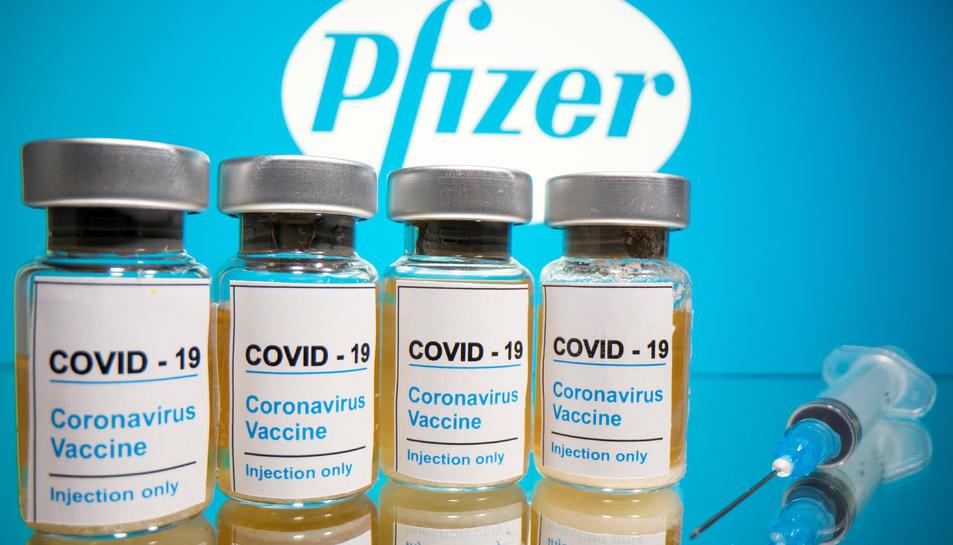 Vials amb l'etiqueta 'COVID-19 / vacuna contra el coronavirus / només per injecció' i una xeringa mèdica davant del logotip de Pfizer