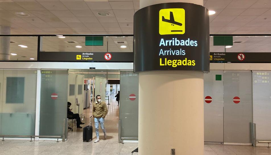 Un senyal de la zona d'Arribades amb un passatger arrossegant una maleta de fons a l'Aeroport del Prat