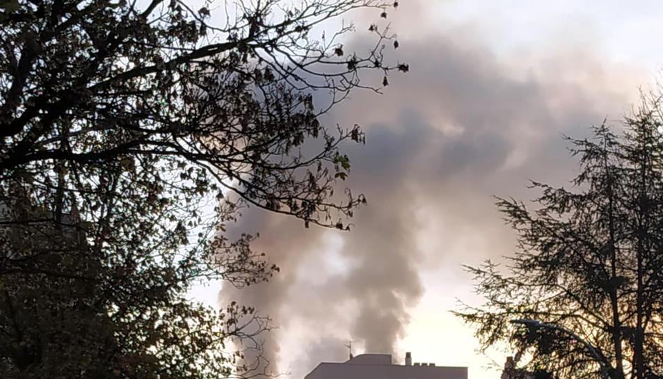 El fum surt a l'exterior en l'incendi d'un habitatge en un edifici al carrer d'en Joan Reglà de Girona