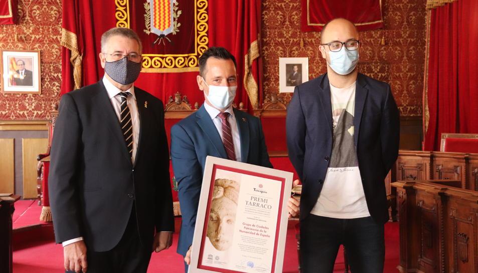 El president del Grup de Ciutats Patrimoni de la Humanitat, Rafael Ruiz, mostra el Premi Tàrraco acompanyat de l'alcalde de Tarragona, Pau Ricomà i del conseller de Patrimoni, Hermán Pinedo.
